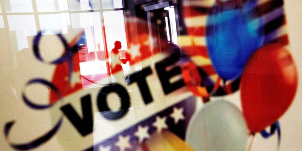 Loading A voter is reflected in the glass frame of a poster while leaving a polling site in Atlanta, during early voting ahead of the November 8 election day. Photo / AP