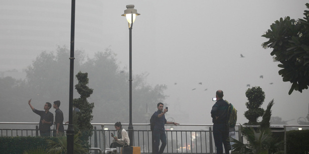 People take selfies at a public park enveloped by thick smog in New Delhi. Photo / AP