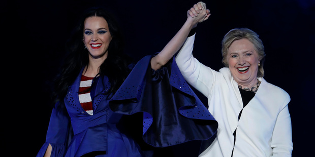 Katy Perry, left, holds the hand of Democratic presidential candidate, Hillary Clinton, right, during a concert in Philadelphia. Photo / AP