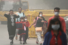 An Indian family arrives at a protest against air pollution in New Delhi. Photo / AP
