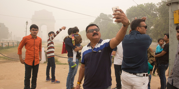 Indian tourists take selfies against the war memorial India Gate engulfed in smog in New Delhi. Photo / AP
