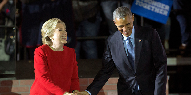 President Barack Obama and Democratic presidential candidate Hillary Clinton hold hands as they walk off stage after both spoke at a rally. Photo / AP