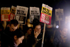 A woman holding a placard wipes away tears as she takes part in an anti-racism protest against President-elect Donald Trump winning the American election, outside the U.S. embassy in London. Photo/AP