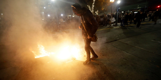 Loading A protester walks next to a fire set by fellow protesters in Oakland, California. Photo / AP