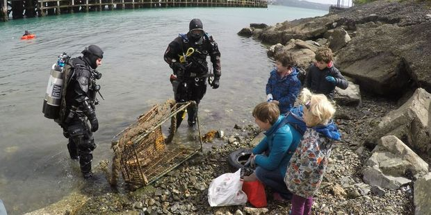 Divers and kids work on cleaning up Miramar Wharf. Photo/supplied