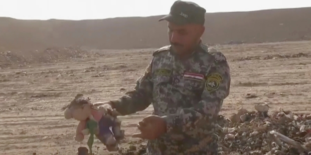 An Iraqi officer holds up a soft toy found in a mass grave in the town of Hamam al-Alil. Photo / AP