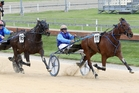 Monbet beats his stablemate Quite A Moment in the Dominion Trot at Addington yesterday in national record time.