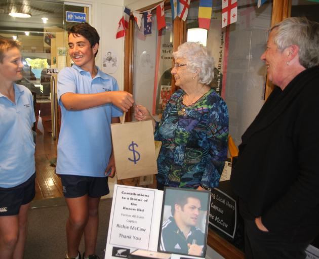 Waitaki Valley School pupils (from left) William Smillie (12) and Tama Chapman (12) hand over $100, the results of a school fundraiser for the Richie McCaw statue, to Kurow Museum volunteer Agnes Mansfield and museum and information centre co-ordinator Carron Cossens. Photo / Shannon Gillies