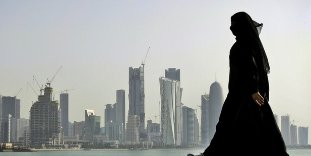 A Qatari woman walks in front of the city skyline in Doha, Qatar. Photo / AP