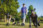 Andy takes two pups, including his boyfriend Scamp, right, for a walk in Croydon park.