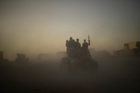 Iraqi troops drive through the dust as they enter Mosul yesterday as they battle to take the city from Isis. Picture / AP