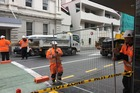 Council contractors at the scene on Tory Street putting up a temporary fence to block the area off overnight. Photo / Susan Strongman