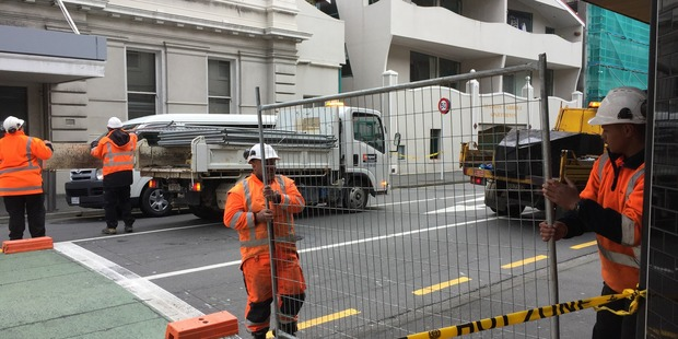 Council contractors on Tory Street putting up a temporary fence to block the area off overnight. Photo / Susan Strongman