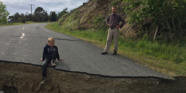 Jack Satterthwite, 10, sits on the lip of a large crack in the road in Waiau caused by the earthquake. Photo / Supplied