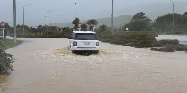 Loading A vehicle negotiating floodwater across State Highway One at the Plimmerton Roundabout north of Wellington. Photo / Mark Mitchell