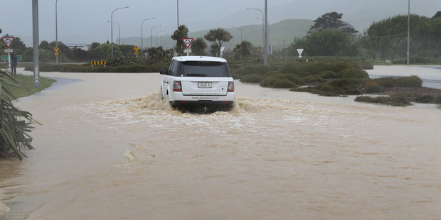 A vehicle negotiates floodwaters across State Highway One at the Plimmerton Roundabout north of Wellington on Tuesday. Photo/Mark Mitchell.