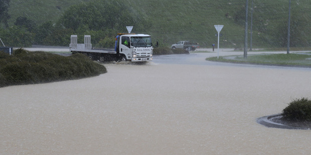 A truck negotiates floodwater across State Highway One at the Plimmerton Roundabout north of Wellington. Photo / Mark Mitchell