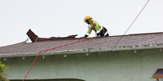 Firefighter Daniel Townsend officer fixes a roof in Helmore Street, Whanganui.