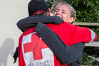 Doug Winter from the Red Cross disaster response team gets a grateful hug from English tourist Amy Cook after she is told she will be evacuated from Kaikoura. Photo / Mike Scott
