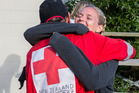 Amy Cook gives Doug Winter from the Red Cross disaster response team a grateful hug after she finds out she is getting flown from Kaikoura. Photo / Mike Scott