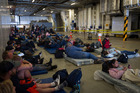 About 150 refugees make themselves comfortable on the HMNZS Canterbury for their evacuation to Lyttelton this morning. Photo / New Zealand Defence Force