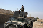 An Iraqi special forces soldier stands atop a Humvee in the village of Bazwaya, some 8 kilometers from the center of Mosul, Iraq. Photo / AP