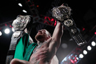 Conor McGregor holds up his title belts after he defeated Eddie Alvarez last weekend. Photo / AP