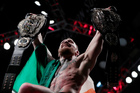 Conor McGregor holds up his title belts after he defeated Eddie Alvarez during a lightweight title mixed martial arts bout at UFC 205. Photo / AP