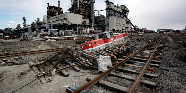 A train rests in a sink hole near a factory in Ishinomako, Japan, two weeks a tsunami hit as a result of a 9.1 earthquake on March 11, 2011. Photo / NZPA / Bradley Ambrose