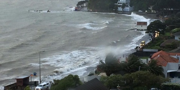 Waves going over the road at Lowry Bay. Photo / Facebook
