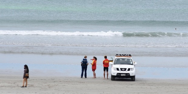 Lifeguards talk with police at Mount Maunganui main beach as they search for a missing kayaker. Photo/George Novak
