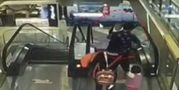 CCTV footage from China shows a grandmother stepping onto a department store's moving staircase with her 4-month-old grandson in her arms. Photo / via YouTube