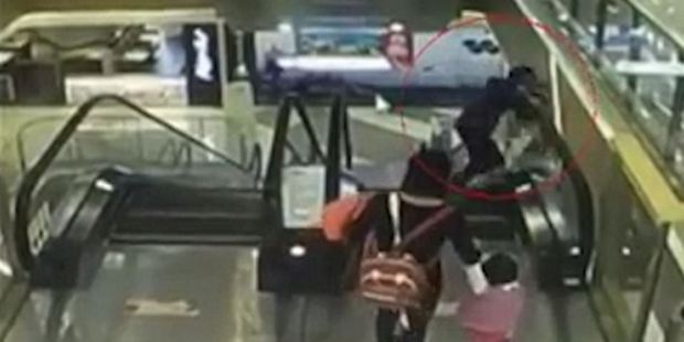 She accidentally loses her grip on her infant grandson who is flung over the edge of the escalator. Photo / via YouTube