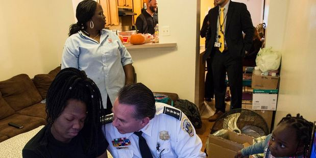 Interim D.C. Police Chief Peter Newsham comforts LaKira as her mother, Cassandra Johnson, and her daughter Kali hover beside her air mattress in October. Photo: Nikki Kahn, The Washington Post.