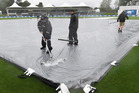 Ground staff clear water from the playing field. Photosport