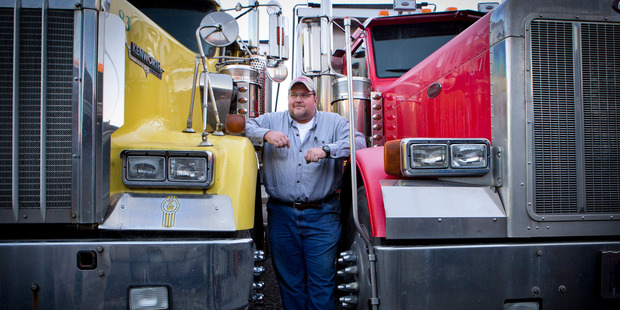 Ricky Meade, 47, owner of Double R Trucking, stands between his trucks in Coeburn, Va. Photo by Julia Rendleman for The Washington Post