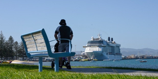 A Mount Maunganui walker enjoys Pilot Bay with an extra large visitor docking in the background. The Celebrity Solstice is the first cruise ship to spend overnight in Tauranga. Photo/George Novak
