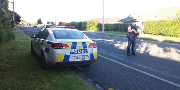 Armed police block the road in Poike, Tauranga, as a police operation gets underway. Photo/Stuart Whitaker