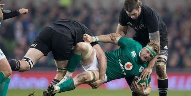 Loading All Blacks Brodie Retallick and Liam Squire tackles Irish No.8 Jamie Heaslip. Photo / Brett Phibbs