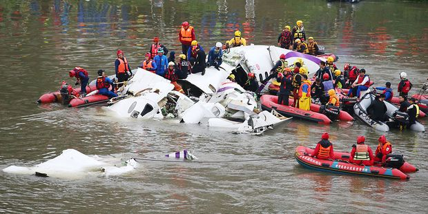 Rescue teams work to free passengers from a TransAsia Airways ATR 72-600 turboprop airplane that crashed into the Keelung River on February, 2015. Photo / Getty Images