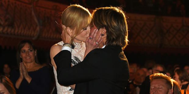 Nicole Kidman kisses husband Keith Urban as she celebrates winning the Best Actress award. Photo / Getty