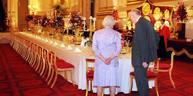 Queen Elizabeth II, accompanied by Sir Hugh Roberts in the Ballroom which has been set out so that visitors can experience a State Banquet. Photo / Getty Images