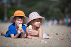 Tristan Duncan-Sutherland, 6, and Amaia Duncan-Sutherland, 4, enjoy an icecream on Mission Bay beach, Auckland. Photo / Chris Loufte