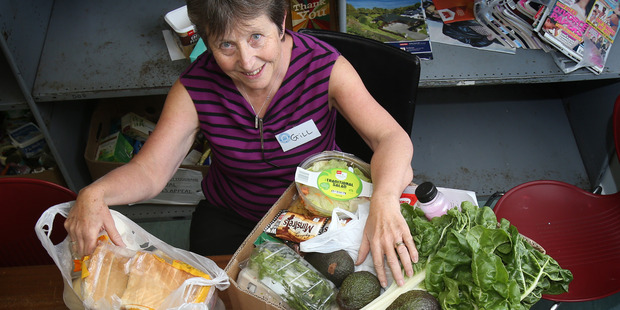 Loading Tauranga Community food bank volunteer, Gill Hosie, with what goes into a food parcel. Photo / John Borren