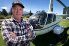 Helicopter pilot Joe Tripp pictured with his helicopter at Kaikoura Airport today. Photo / Alan Gibson