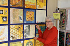 Merrilyn George adds Catherine McDonald's work to the quilt exhibition in Ohakune.
