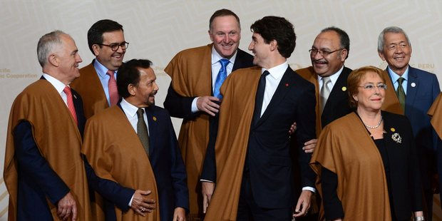 John Key enjoys a bit of horseplay with Canadian Prime Minister Justin Trudeau - japing about in Peruvian shawls. Picture / The Canadian Press