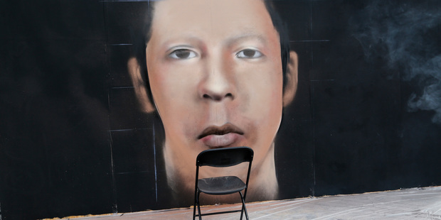 An empty folding chair stands next to a mural depiction of a missing young man during a demonstration in Mexico City today. Photo / AP
