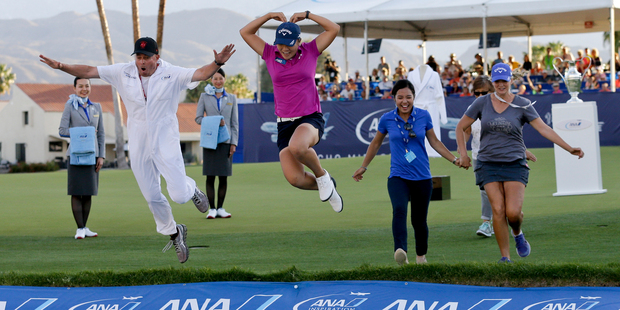 Ko and her caddie Jason Hamilton jump into Poppie's Pond after winning the ANA Inspiration. Photo / AP