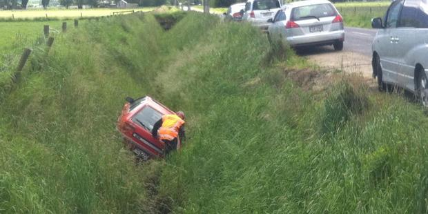 A tow truck driver salvages a Mitsubishi Mirage from a ditch beside a line of vehicles parked in Miller Rd near Dunedin Airport on Wednesday. Photo / Gerard O'Brien